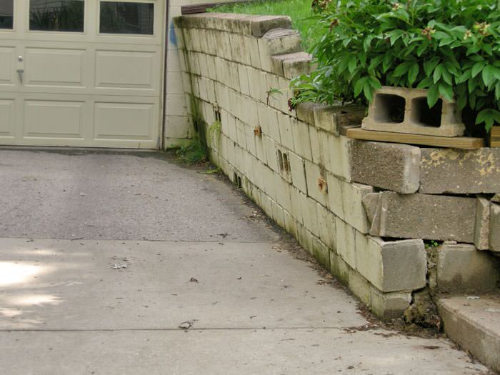 a failing retaining wall around a driveway in Saint Albans