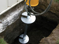 Installing a helical pier system in the earth around a foundation in Beckley