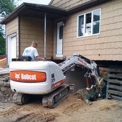 Excavating to expose the foundation walls and footings for a replacement job in Hurricane