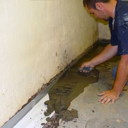 A basement waterproofer installing a perimeter drain system in Elkview